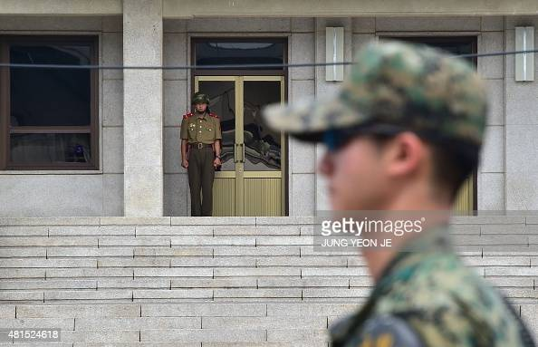 A South Korean soldier stands guard as a North Korean soldier looks on at the truce village of Panmunjom in the Demilitarized zone dividing the two...