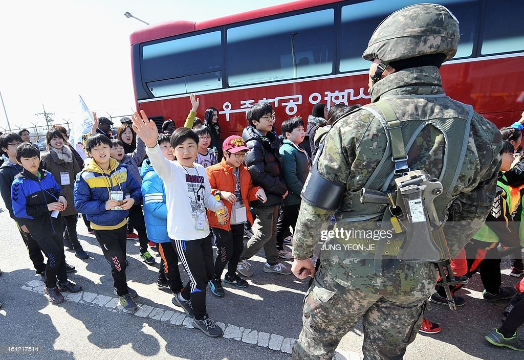 A South Korean soldier (R) stands guard as children march on the road linked to North Korea at a military check point in Paju near the Demilitarized Zone (DMZ) dividing the two Koreas on March 21, 2013 during a campaign for a peace forest on the tense inter-Korean border. Sixteen-year-old Korean-American Jonathan Lee, an environmental and peace activist, spearheaded this campaign and wanted the international community to agree to have children from both sides meet and create a Children's Peace Park in the DMZ. AFP PHOTO / JUNG YEON-JE
