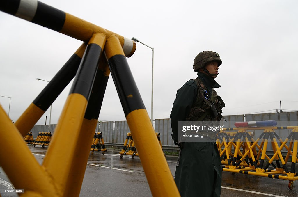 A South Korean soldier stands guard at a military check point on the Unification Bridge, linked to North Korea, near the demilitarized zone (DMZ) in Paju, South Korea, on Friday, July 12, 2013. North Korea notified South Korea today that it has deferred two separate sets of talks on the tours and the family reunions it proposed yesterday, and said it wants to focus on the ongoing dialog to reopen the joint Gaeseong industrial zone, the Souths Unification Ministry said in an e-mailed statement. The two sides yesterday decided to hold talks in Gaeseong on July 15, which will be their third round in one week, on normalizing operations in Gaeseong after the North unilaterally recalled its workers in April. Photographer: SeongJoon Cho/Bloomberg via Getty Images