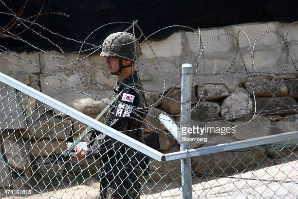 A South Korean soldier stands guard behind a fence near the Second Tunnel an 'infiltration' tunnel dug by North Korea near the demilitarized zone in...