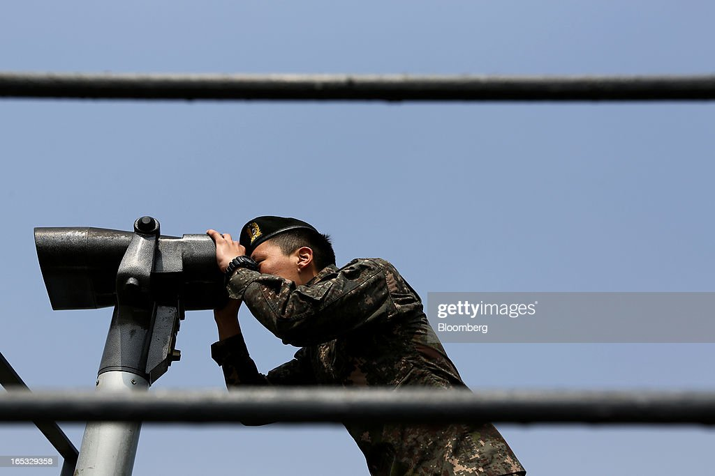 A South Korean soldier uses binoculars as he looks across to the north side of the border at the Imjingak pavilion near the demilitarized zone (DMZ) in Paju, South Korea, on Wednesday, April 3, 2013. North Korea prevented South Korean workers from entering a jointly run industrial park today, adding to tensions after saying it will restart a mothballed nuclear plant and threatening to attack its southern neighbor. Photographer: SeongJoon Cho/Bloomberg via Getty Images