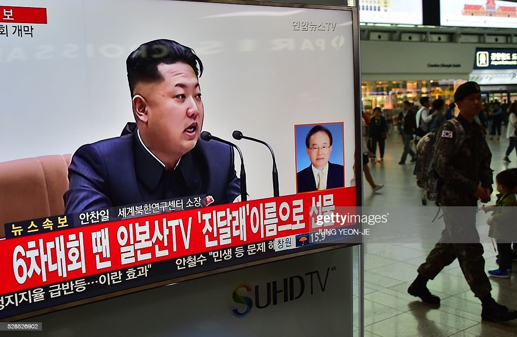 A South Korean soldier (R) walks past a television screen showing file footage of North Korean leader Kim Jong-Un, at a railway station in Seoul on May 6, 2016. North Korea raised the curtain on May 6 on its biggest political show for a generation, aimed at cementing the absolute rule of leader Kim Jong-Un and shadowed by the possibility of an imminent nuclear test. / AFP / JUNG
