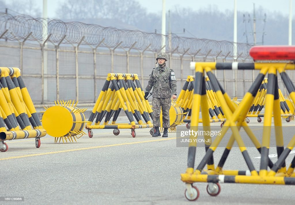 A South Korean soldier walks past barricades a military check point on the road linked to North Korea in Paju near the Demilitarized Zone (DMZ) on April 1, 2013. South Korean workers and cargo on April 1 headed for the Kaesong Industrial Complex without a hitch despite North Korea's recent threat to close the joint industrial zone in the communist country.