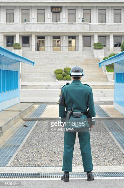 A South Korean soldier watches a North Korean building at the truce village of Panmunjom in the demilitarised zone on April 23 2013 Tensions simmer...