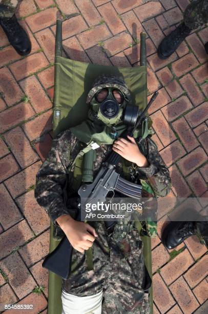 A South Korean soldier wearing a gas mask participates in a decontamination training at a stadium in Seoul on September 27 2017 The training is...