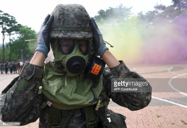 A South Korean soldier wears a gas mask during a decontamination training at a stadium in Seoul on September 27 2017 The training is designed to...