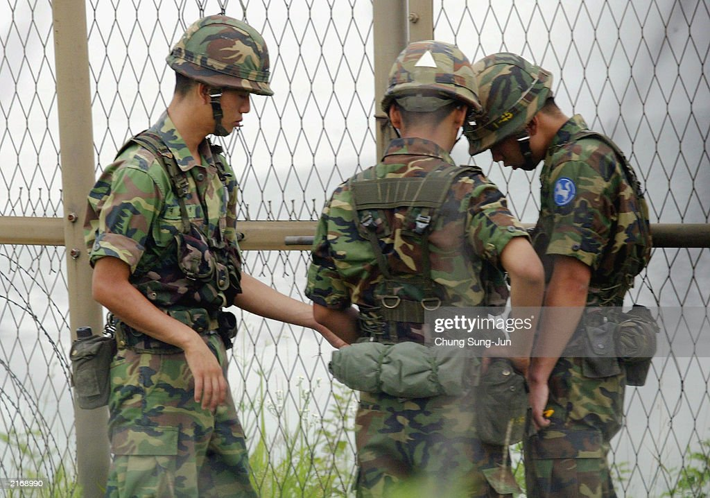 South Korean soldiers check the barbed wire fence near the Demilitarized Zone in Paju which separates South and North Korea on July 17 2003 North of...