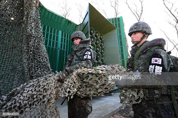 South Korean soldiers drow down a cover from the loudspeakers at a military base near the border between South Korea and North Korea on January 8...