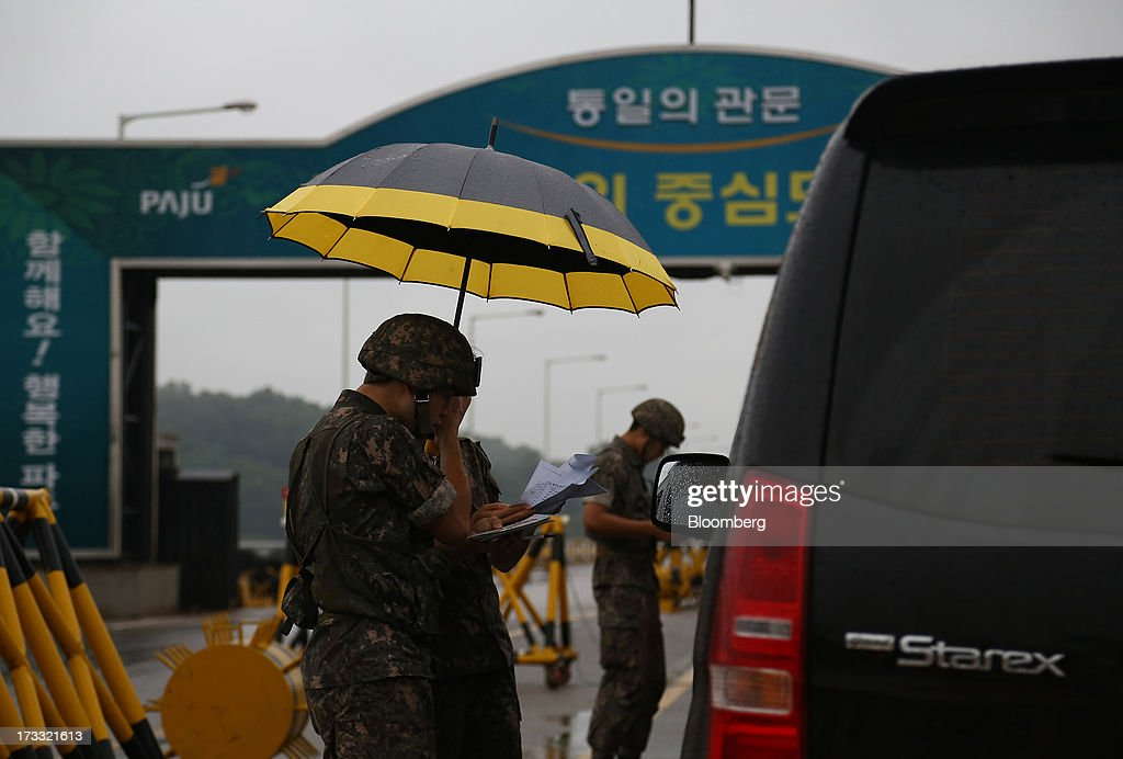 South Korean soldiers inspect vehicles at a military check point on the Unification Bridge, linked to North Korea, near the demilitarized zone (DMZ) in Paju, South Korea, on Friday, July 12, 2013. North Korea notified South Korea today that it has deferred two separate sets of talks on the tours and the family reunions it proposed yesterday, and said it wants to focus on the ongoing dialog to reopen the joint Gaeseong industrial zone, the Souths Unification Ministry said in an e-mailed statement. The two sides yesterday decided to hold talks in Gaeseong on July 15, which will be their third round in one week, on normalizing operations in Gaeseong after the North unilaterally recalled its workers in April. Photographer: SeongJoon Cho/Bloomberg via Getty Images