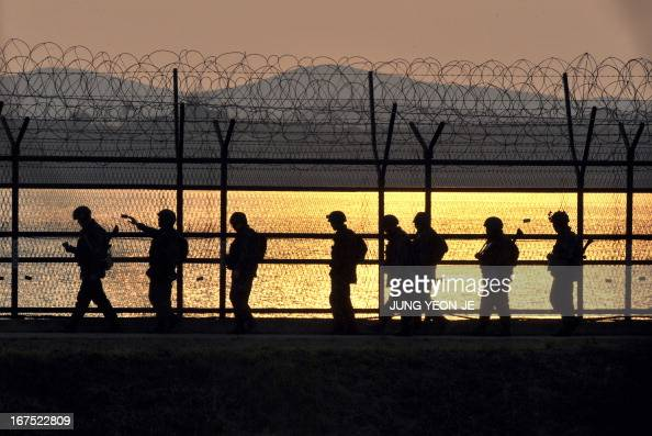 South Korean soldiers patrol along a military fence near the Demilitarized Zone dividing the two Koreas in the border city of Paju on April 26 2013...