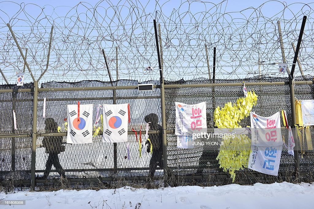 South Korean soldiers patrol along a military iron fence hanging 'reunification ribbons' at Imjingak peace park in Paju near the demilitarized zone dividing the two Koreas on February 13, 2013. South Korea said on February 13 it would accelerate the development of longer-range ballistic missiles that could cover the whole of North Korea in response to a third nuclear test by Pyongyang.