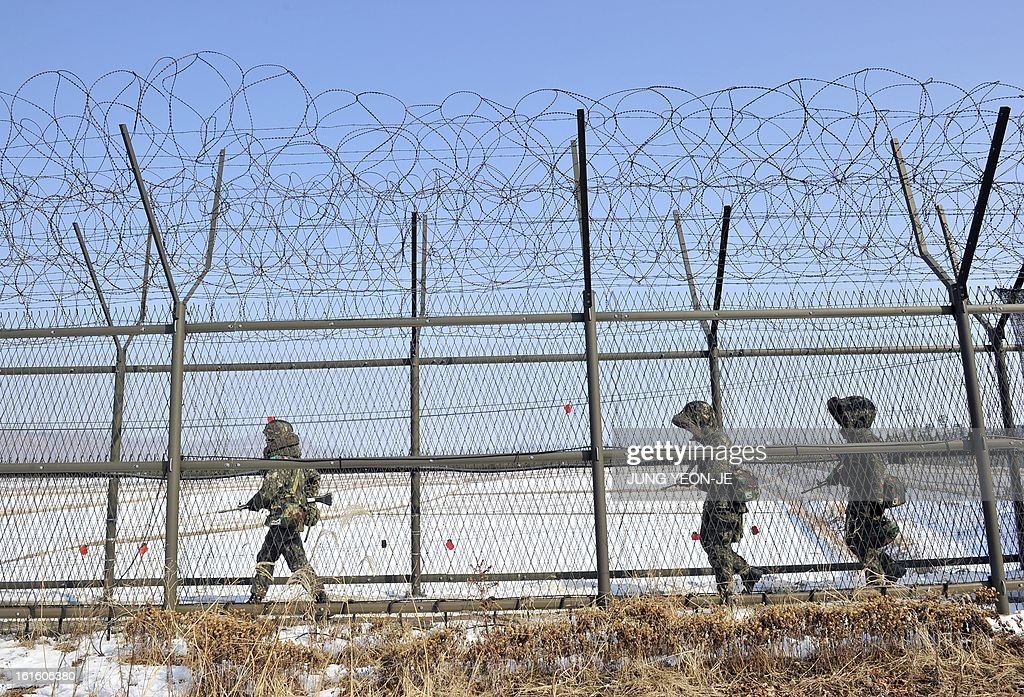 South Korean soldiers patrol along a military iron fence in Paju near the demilitarized zone dividing the two Koreas on February 13, 2013. South Korea said on February 13 it would accelerate the development of longer-range ballistic missiles that could cover the whole of North Korea in response to a third nuclear test by Pyongyang. AFP PHOTO / JUNG YEON-JE