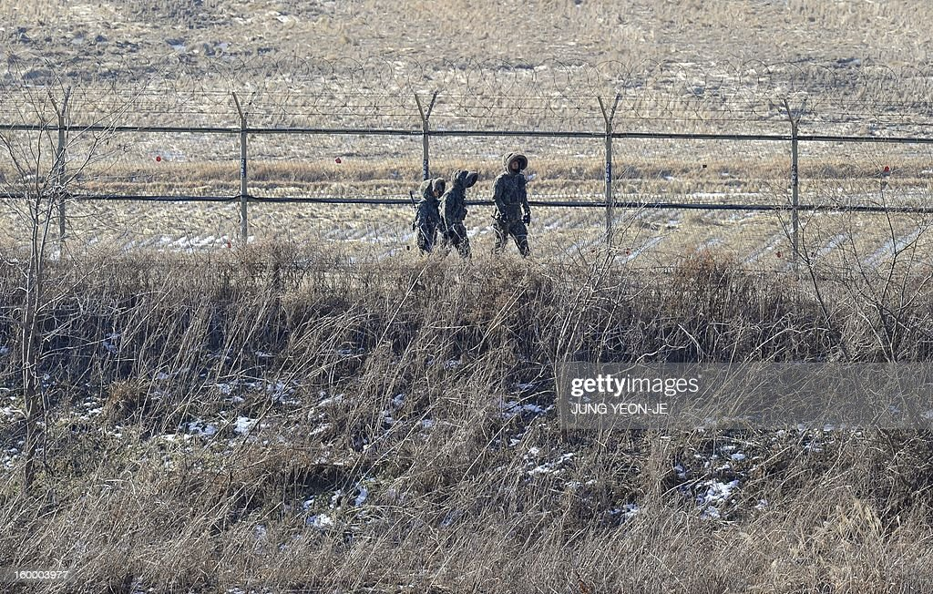 South Korean soldiers patrol along military iron fence in Paju near the Demilitarized Zone (DMZ) dividing the two Koreas on January 25, 2013. North Korea on January 25 threatened 'physical counter-measures' against rival South Korea, the latest in a series of bellicose warnings sparked by a tightening of UN sanctions against Pyongyang.