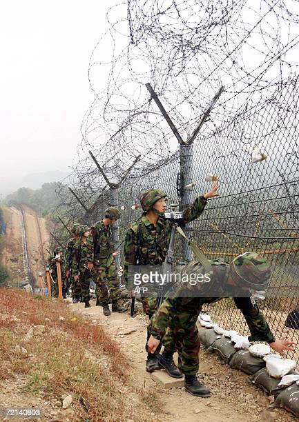 South Korean soldiers patrol along the barbed wire fence near an observation point on the southern side of the Demilitarized Zone dividing North and...