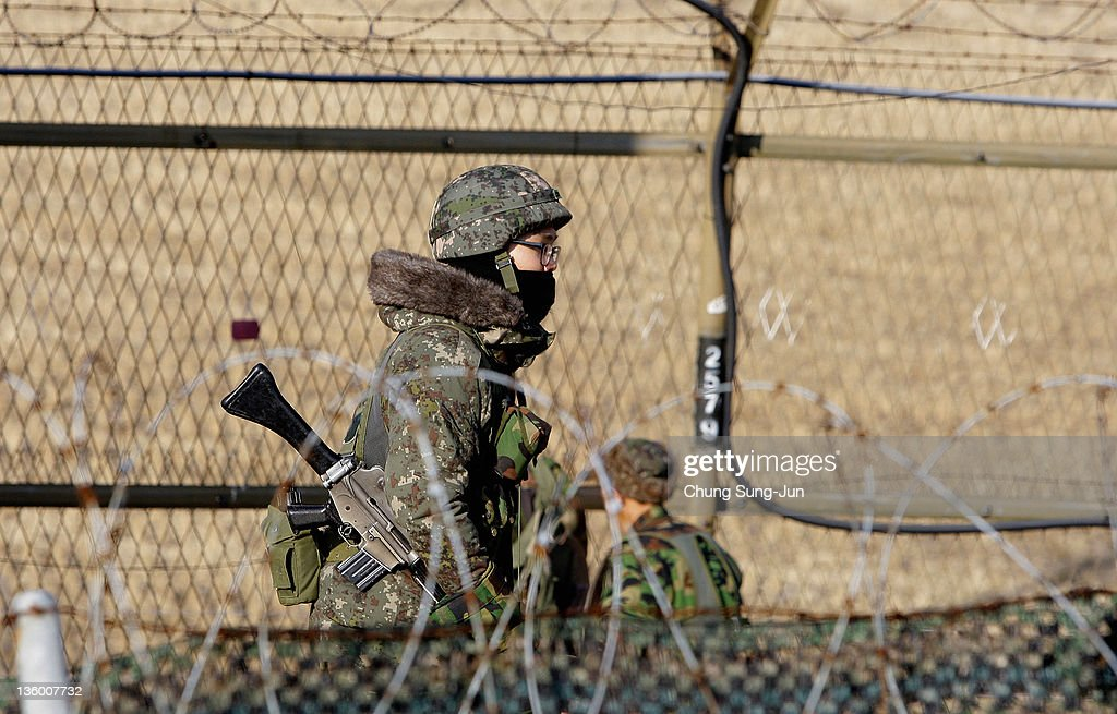 South Korean soldiers patrol inside the barbedwire fence at Imjinkak near the Demilitarized zone separating South and North Korea on December 20 2011...