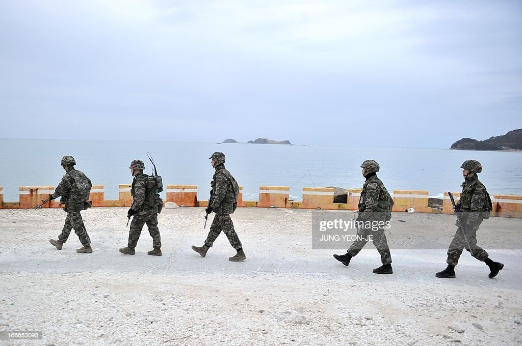 South Korean soldiers patrol on the Southcontrolled island of Yeonpyeong near the disputed waters of the Yellow Sea at dawn on April 15 2013 The...