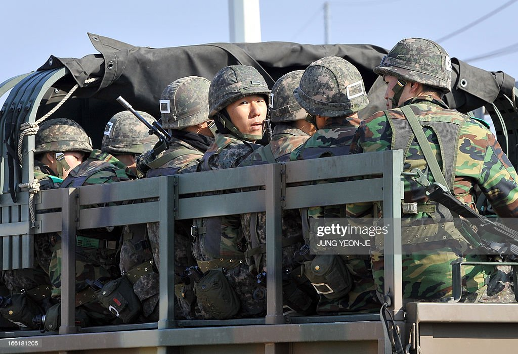 South Korean soldiers ride a military truck on the road leading to North Korea at a military checkpoint in the border city of Paju on April 10, 2013. South Korea and the United States upgraded their coordinated military surveillance status on April 10, a report said, ahead of an expected mid-range missile launch by North Korea. AFP PHOTO / JUNG YEON-JE