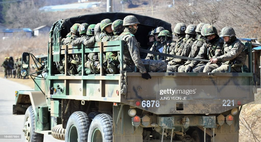 South Korean soldiers ride on a military truck in the border city of Paju on March 29, 2013. North Korean leader Kim Jong-Un ordered preparations on March 29 for strategic rocket strikes on the US mainland and military bases after US stealth bombers flew training runs over South Korea. AFP PHOTO / JUNG YEON-JE