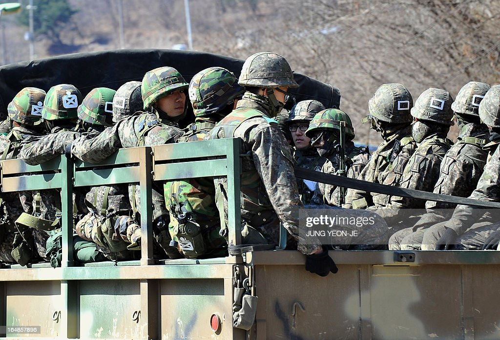 South Korean soldiers ride on a military truck in the border city of Paju on March 29, 2013. North Korean leader Kim Jong-Un ordered preparations on March 29, for strategic rocket strikes on the US mainland and military bases after US stealth bombers flew training runs over South Korea. AFP PHOTO / JUNG YEON-JE
