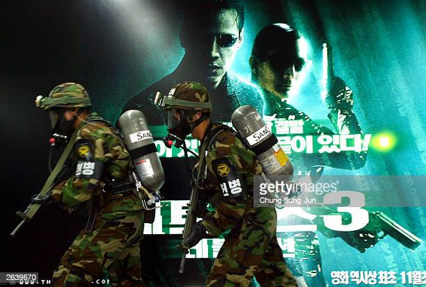 South Korean soldiers run past a billboard poster for The Matrix during an antichemical attack drill at a subway station October 24 2003 in Seoul...