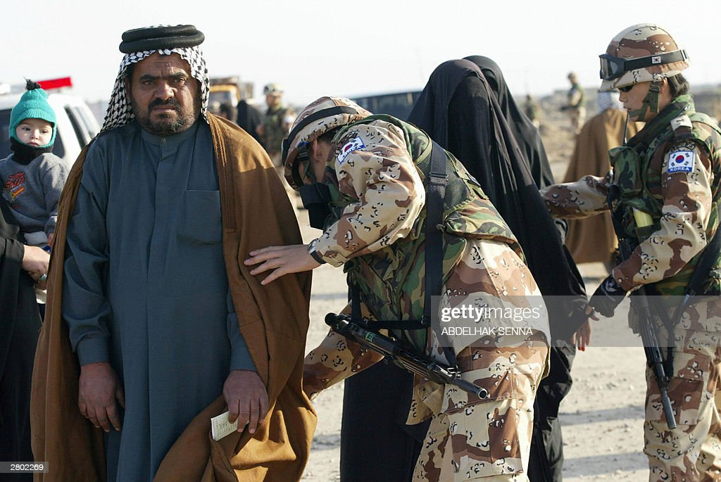 South Korean soldiers search an Iraqi family outside the US Tallil air base near the southern city of Nasiriyah 11 December 2003 Hundreds of Iraqis...
