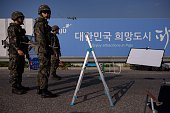South Korean soldiers stand before a checkpoint on the Unification Bridge that leads to the Demilitarized Zone between North and South Korea in Paju...