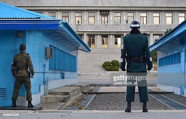South Korean soldiers stand guard as a North Korean soldier is seen at the truce village of Panmunjom in the Demilitarized Zone dividing the two...
