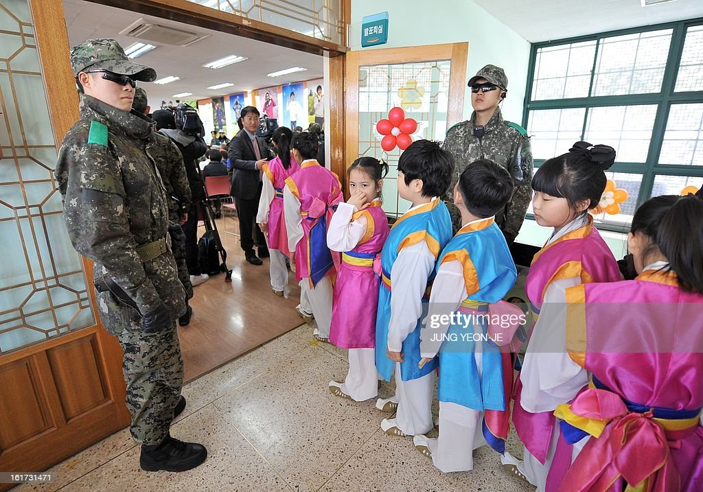 South Korean soldiers stand guard as students enter the hall during a graduation ceremony for Taesungdong Elementary School at Taesungdong freedom village near the border village of Panmunjom in Paju on February 15, 2013. Six students graduated from the only school in this South Korean village sitting inside the demilitarized zone between North and South Korea where a total of 30 students study under a heavy military presence.