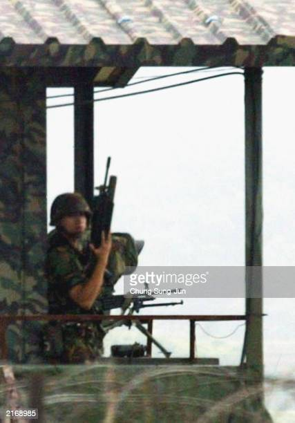 South Korean soldiers stand guard at an observation post near the Demilitarized Zone in Paju which separates South and North Korea on July 17 2003...