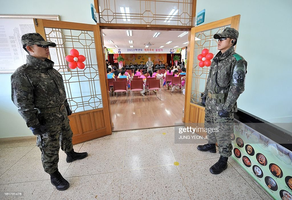 South Korean soldiers stand guard ouside the hall during a graduation ceremony for Taesungdong Elementary School at Taesungdong freedom village near the border village of Panmunjom in Paju on February 15, 2013. Six students graduated from the only school in this South Korean village sitting inside the demilitarized zone between North and South Korea where a total of 30 students study under a heavy military presence. AFP PHOTO / POOL / JUNG YEON-JE