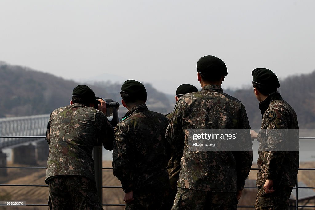 South Korean soldiers use binoculars as they look across to the north side of the border at the Imjingak pavilion near the demilitarized zone (DMZ) in Paju, South Korea, on Wednesday, April 3, 2013. North Korea prevented South Korean workers from entering a jointly run industrial park today, adding to tensions after saying it will restart a mothballed nuclear plant and threatening to attack its southern neighbor. Photographer: SeongJoon Cho/Bloomberg via Getty Images