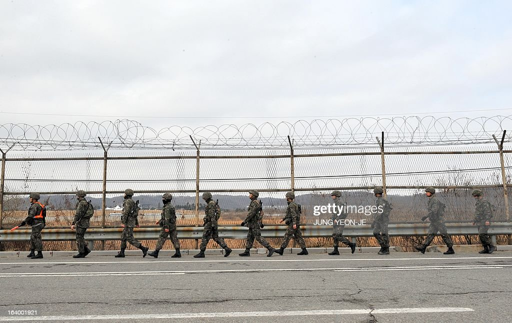 South Korean soldiers walk along an iron fence near a military check point in the border city of Paju on March 19, 2013. The US on March 19 said it was flying training missions of nuclear-capable B-52 bombers over South Korea, in a clear signal to North Korea at a time of escalating military tensions. AFP PHOTO / JUNG YEON-JE