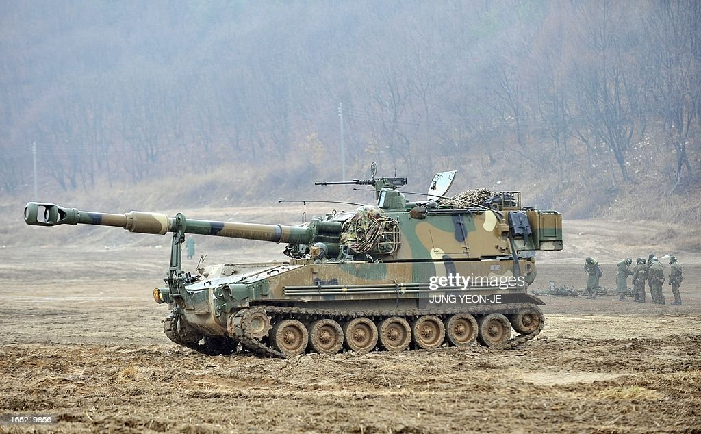 South Korean soldiers (R) wear gas masks as a K-55 self-propelled howitzer (C) drives past at a military training field on the border city of Paju on April 2, 2013. South Korea's new president on April 1 promised a strong military response to any North Korean provocation after Pyongyang announced that the two countries were now in a state of war.