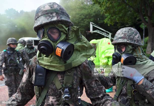 South Korean soldiers wear gas masks during a decontamination training at a stadium in Seoul on September 27 2017 The training is designed to train...