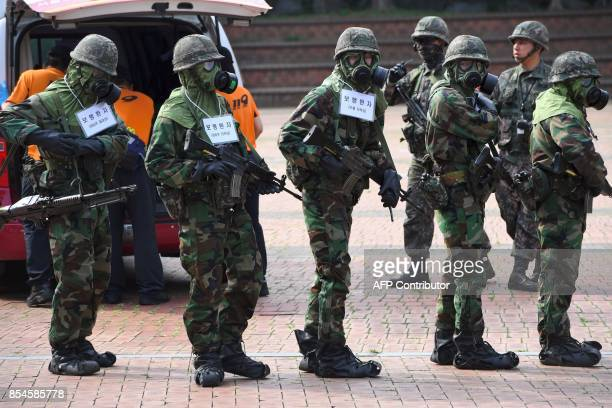 South Korean soldiers wearing chemical protective gears participate in a decontamination training at a stadium in Seoul on September 27 2017 The...