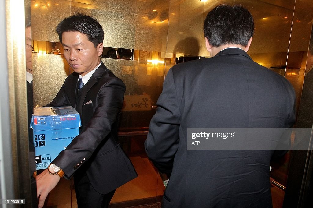 A South Korean special prosecutor officer carries confiscated articles from the home of Lee Sang-Eun, President Lee Myung-Bak's eldest brother, in Seoul on on October 17, 2012. South Korean investigators on October 17 raided the home and office of President Lee Myung-Bak's eldest brother as part of a probe into alleged irregularities in a project to build Lee's retirement home. The raid came a day after a special prosecutor requested that Lee's only son, Lee Si-Hyung, and 10 other people linked to the now-defunct project be barred from leaving the country. REPUBLIC