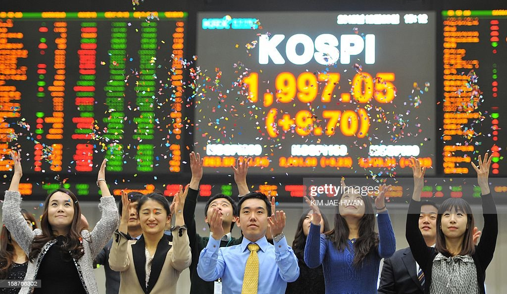 South Korean stock market staff scatter confetti during a ceremony marking the closure of 2012 trading year in Seoul on December 28, 2012. The benchmark KOSPI index closed the year at 1,997.05, up 9.4 percent from a year ago, despite a global economic slowdown.