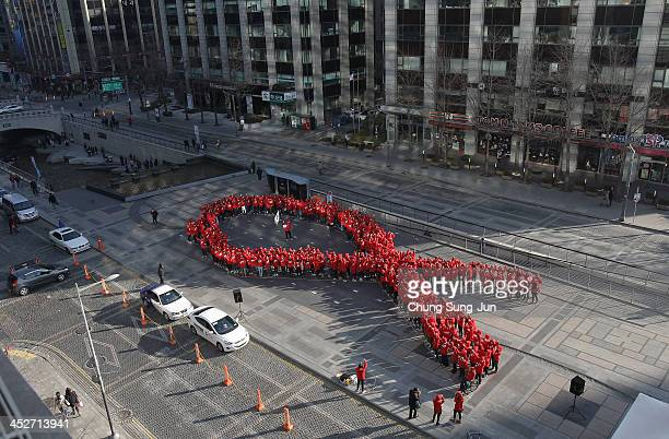 South Korean students pose in the shape of the 'aids ribbon' during an event to promote the awareness of Aids at Cheonggyecheon on December 1 2013 in...