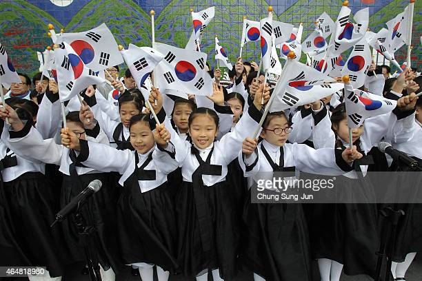 South Korean students wearing traditional costume wave national flags during the celebration of Independence Movement Day on March 1 2015 in Seoul...