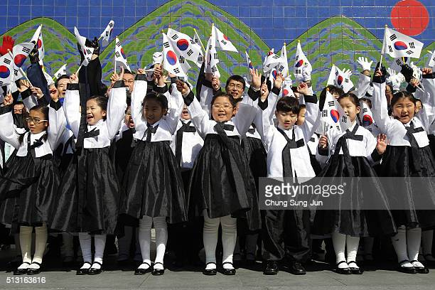South Korean students wearing traditional costume wave national flags during the celebration of 97th Independence Movement Day on March 1 2016 in...