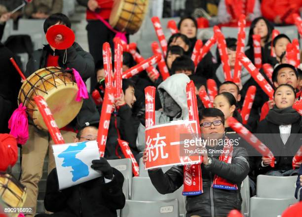 A South Korean supporter holds the Unification flag during the EAFF E1 Men's Football Championship between North Korea and South Korea at Ajinomoto...