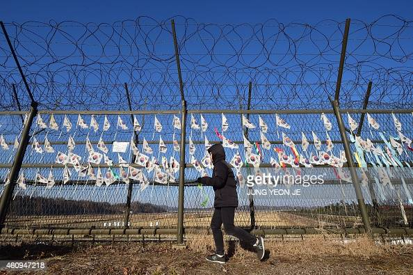 A South Korean tourist walks along a military barbed wire fence decorated with national flags at the Imjingak peace park at the border city of Paju...