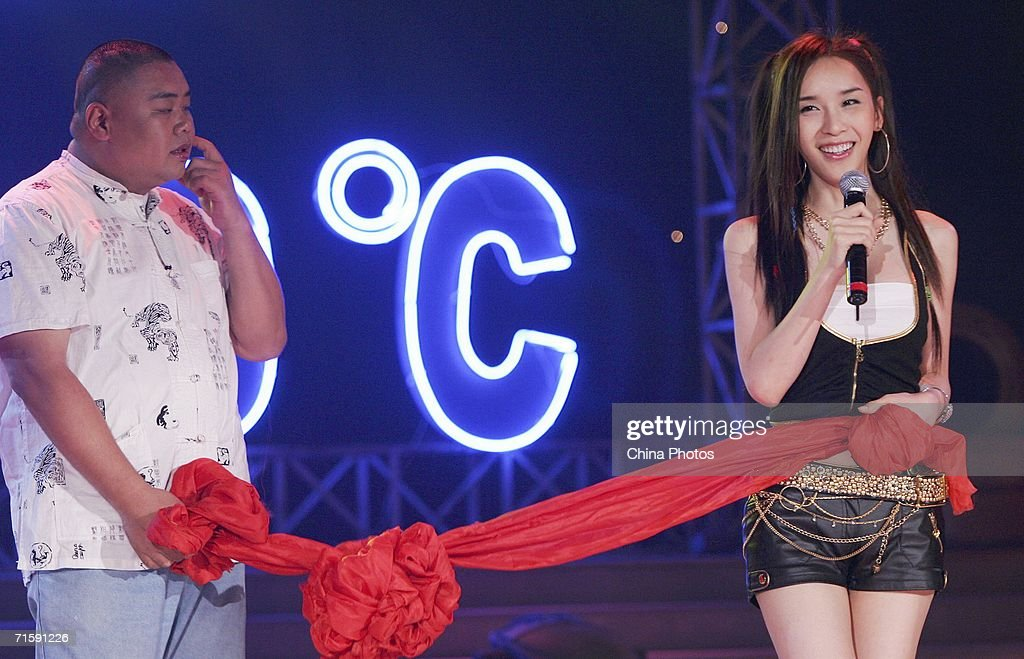 South Korean transsexual singer and actress Harisu poses for pictures with a fan who played the role of groom during a simulated Chinese wedding at a...