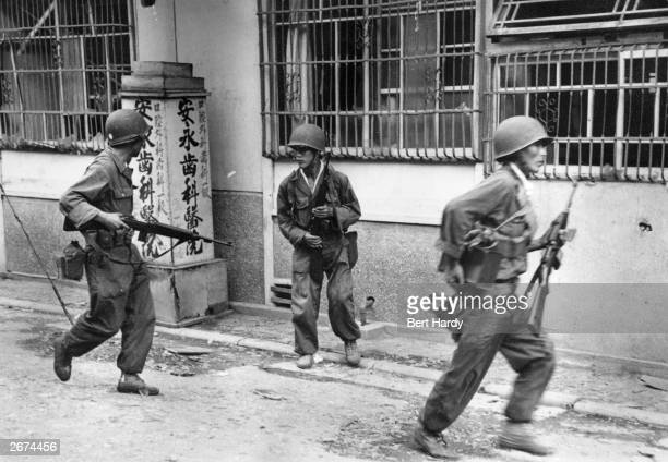 South Korean troops in the streets of Inchon with guns at the ready following the invasion of the town by United Nations forces Original Publication...