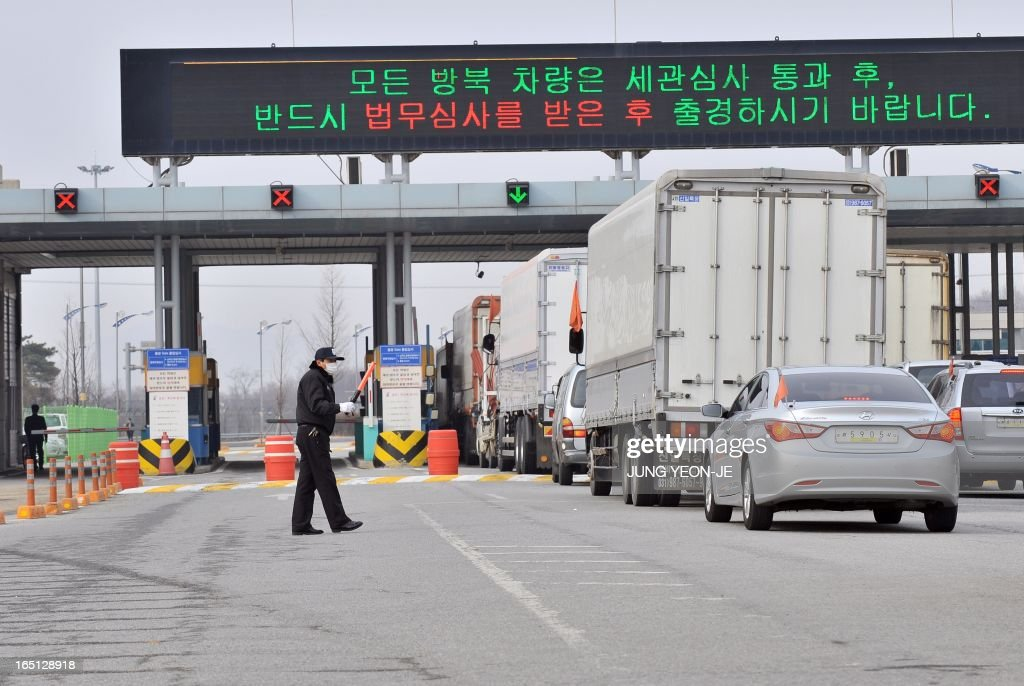 South Korean trucks and vehicles pass a gate to leave for North Korea at the inter-Korean transit office in Paju near the Demilitarized Zone (DMZ) on April 1, 2013. South Korean workers and cargo on April 1 headed for the Kaesong Industrial Complex without a hitch despite North Korea's recent threat to close the joint industrial zone in the communist country. AFP PHOTO / JUNG YEON-JE