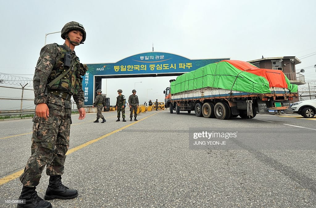 South Korean trucks carrying 500 tons of flour for North Korean flood victims drive past a military checkpoint near the inter-Korean border in Paju, north of Seoul, on September 21, 2021. A Seoul charity group sent flood aid to North Korea since the communist state was hit by a string of deadly floods and typhoons this summer.