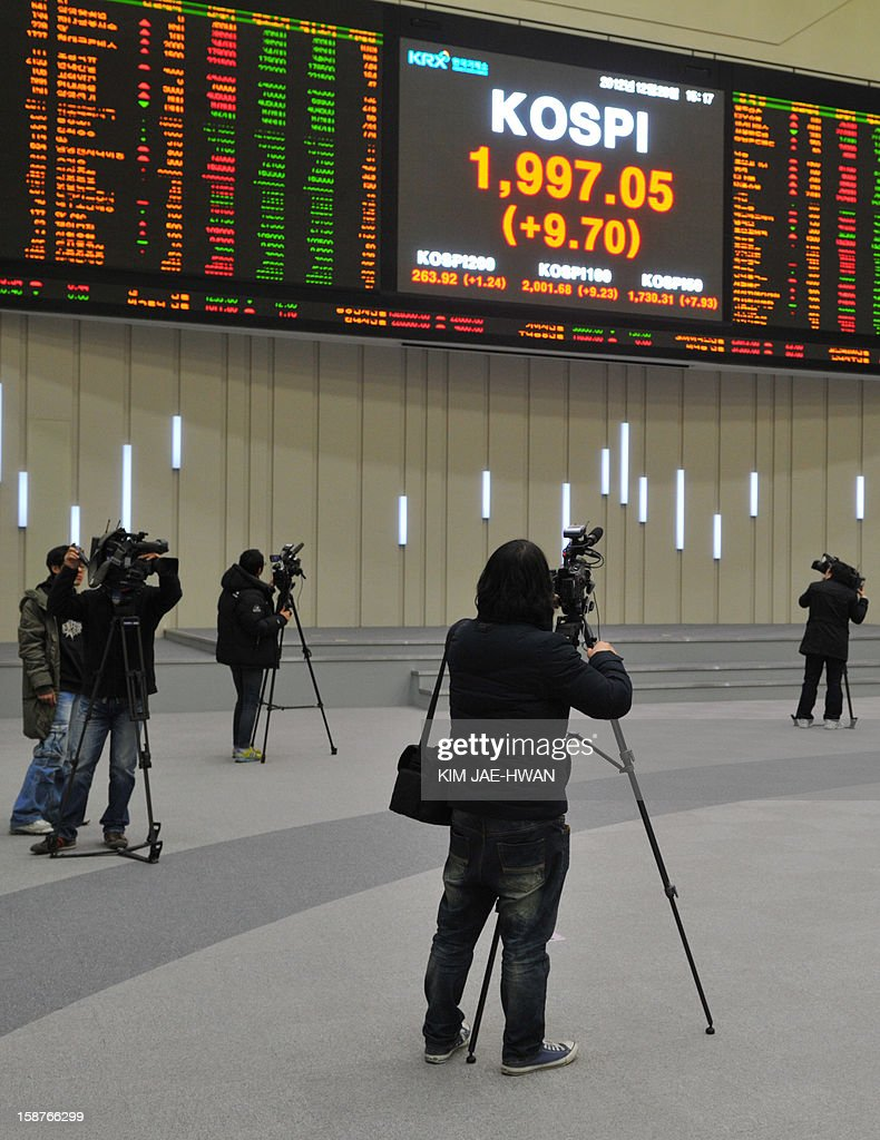 South Korean TV crew film an electronic board showing the closing prices of shares on the final day of the 2012 trading year in Seoul on December 28, 2012. The benchmark KOSPI index closed the year at 1,997.05, up 9.4 percent from a year ago, despite a global economic slowdown. AFP PHOTO / KIM JAE-HWAN