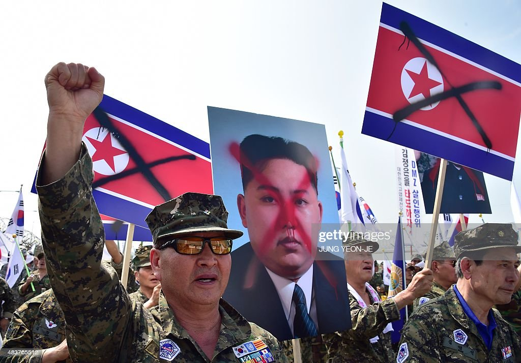 South Korean veterans hold placards showing spray-painted portraits of North Korean leader Kim Jong-Un during an anti-North Korea protest in Paju on August 13, 2015, denouncing a recent landmine attack at a military check point near the Demilitarized Zone dividing the two Koreas. South Korea ramped up border security on August 11, as military tensions flared following landmine blasts blamed on North Korea, and the presidential office in Seoul demanded a formal apology.