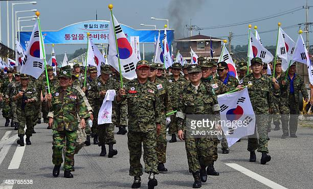 South Korean veterans march with their national flags after an antiNorth Korea protest in Paju on August 13 denouncing a recent landmine attack at a...