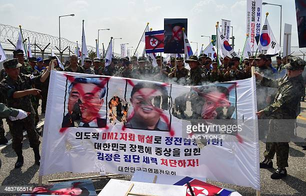 South Korean veterans set fire to a banner showing portraits of North Korean leader Kim JongUn and late leaders Kim IlSung and Kim JongIl during a...